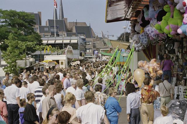 TLB023000198_001 - Overzichtsfoto van Tilburgse Kermis met rechts op de foto het  Kleurenspel met deelnemers. De Tilburgse Kermis is de grootste kermis in de Benelux. Er staan jaarlijks tussen de 230 en 240 attracties uit binnen- en buitenland, in een 4,5 kilometer lang lint door het centrum van de stad. De kermis trekt jaarlijks meer dan een miljoen bezoekers en is daarmee een van de best bezochte evenementen van Nederland.