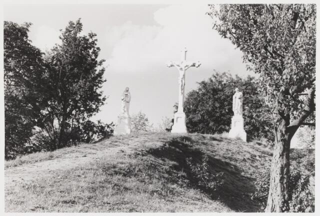 """067879 - De CALVARIEBERG op het kerkhof Bredaseweg. CHRISTUS aan het kruis, geflankeerd door een treurende MARIA en door JOHANNES de EVANGELIST. De gietijzeren Christusfiguur dateert uit 1865 (fa. Mercx, Tilburg). Op het voetstuk van het Mariabeeld is de inscriptie aangebracht: """"Maria, zij dank, moeder is genezen.""""   Trefwoorden: Kunst, openbare ruimte."""