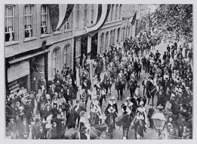 048855 - Bij het 50-jarig bestaan van de N.K. Harmonie trok een stoet door Tilburgs straten. Het begin van deze stoet een Heraut te paard, stelde zich op in de Willem II-straat nabij kapper Lejeune (1e pand links)
