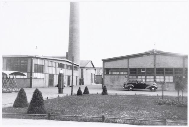 038625 - Volt. Zuid. Gebouwen. 1938. Gezicht vanuit de directiekamer ( gebouw J ) van Volt aan de Nieuwe Goirleseweg (nu Voltstraat). Links gebouw D, de lakspuiterij en rechts gebouw G het Productiebureau later onderdeel van Materials Management. Het gebouw achter de schoorsteen is gebouw E, de machinekamer. De geparkeerde auto is de directieauto.  Voltstraat heette toen Nieuwe Goirleseweg.