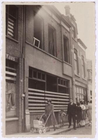 013463 - WOII; WO2; Tweede Wereldoorlog. Oorlogsschade. Vernielingen. Woonhuis in de Noordstraat dat beschadigd werd bij een Duits bombardement op 10 mei 1940. De mensen die voor het pand lopen is het echtpaar Harrie Hovers en Jo Hovers-Schoenmakers en hun kinderen Jan en Gerard.