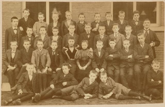 051595 - Klassenfoto. Leerlingen van de school van monsieur Verschuuren. grote groep jongens met in hun midden een (jonge) vrouw en een meisje.
