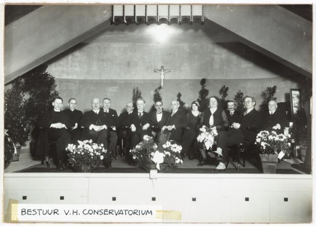 052040 - Hoger Voortgezet Onderwijs. Muziekconservatorium der R.K. Leergangen. 121/2 jarig bestaan van het conservatorium. Bestuur van het conservatorium. Receptie b.g.v. het 121/2 jaar bestaan. v.l.n.r. 1. prof dr. A. Smijers (priester v.d. parochie St. Anna). Hij is directeur belast met de leiding over de kerkmuziek. 2. N.N. 3. Mr. dr. F.L.G.Z.M. Vonk de Both, (burgemeester van Tilburg). 4. W.J. v. Dusseldorp (gemeentesecretaris). 5. Kees Heerkens (docent piano). 6. Dr. Molller (Dr. H.W.E. Moller (ex jezuïet) was de oprichter van de R.K. leergangen in Tilburg op 12 juli 1918.) 7. Leo Heymans (docent viool). 8. Mr. dr. W.J.A. v. Sonsbeeck. 9. mej. Annie Piscaer (docent muziekgeschiedenis). 10. mej. Annie Reyniers (docent piano). 11.  J.C.A.M. v. Mortel (wethouder). 12. W.v. Kalmthout (musicus, componist). Hij is directeur belast met de leiding over de profane muziek. 13. van Oudenhoven (wethouder).