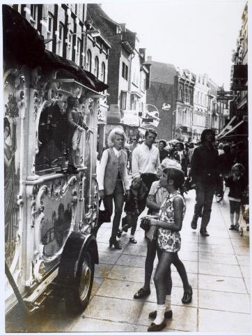 021683 - Jeugdige belangstelling voor een draaiorgel in de Heuvelstraat.