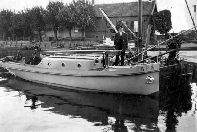 """064882 - Politieboot van de waterpolitie, de RP3.  Deze foto is genomen van de kant waar Aaike van Loon zijn rietheuvel had. De politieboot, gemeerd opzij van een aakje, dat zoals u kunt zien nog vaart met behulp van zeilen, ligt hier vlak voor de sluis van de Vaart.  De man voorop, Christiaan Schrier, is marechaussee/veldwachter in Drimmelen.   De politieman achteraan in de kuip(daar waar men staat te sturen in een klein bootje),  voor is Friedus van den Hoven en de politieman daarachter is Jonkers.  Op de achtergrond ziet men nog een deel van de """"Catharina""""van Jan van de Vaart, in de volksmond Jan Vaartjes genoemd, uit Made. In dit schip staat al een motor.  Het huis op de achtergrond is het café van van Uithoven, later Drik Diepstraten."""