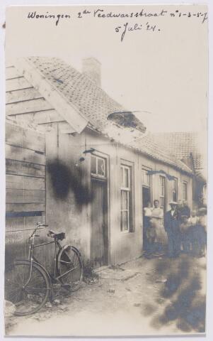 044926 - Ongeveer ter plaatse van de huidige Oeverstraat lag vroeger de Tweede Veedwarsstraat. Op de foto de arbeiderswoningen aan deze straat met de huisnummers 1 t/m 7. De panden werden rond 1924 bewoond door v.l.n.r. arbeider Toon Ebbing, Bart Smetsers, arbeider Jan van den Brand en wever Piet C. van Gorp.