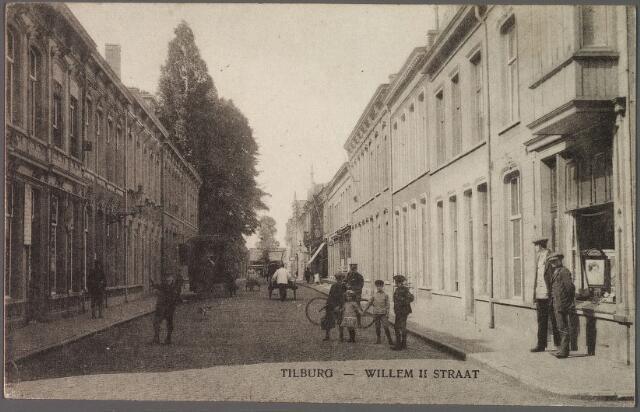 010231 - Willem II-straat richting Spoorlaan. Rechts het hoekpand Willem II-straat/Tuinstraat, N129, vanaf 1910 Willem II-straat 64. Rond 1900 zat hier de firma F.H. Strikkers, winkelier in hoeden en petten. In 1922 vestigde Adriaan Huijbregts zich vanuit de Emmastraat in dit pand. Huijbregts was koek- en suikerbakker. Hij werd geboren te Hooge en Lage Mierde op 30 oktober 1853 en overleed in Tilburg op 14 juli 1931. Zijn vrouw, Lucia Ooms, werd geboren te Tilburg op 11 november 1854 en overleed in haar geboortestad op 30 januari 1936. Het echtpaar was de grondlegger van koekfabriek Huijbregts-Ooms.