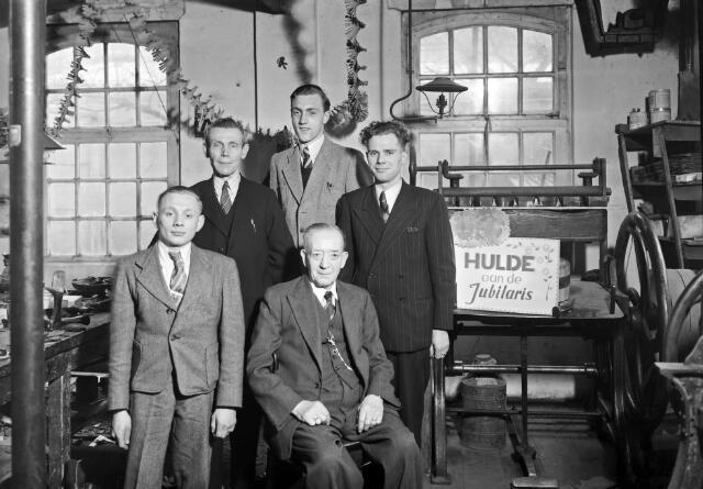 650521 - Schmidlin. De schoenmakerij van L.J. Termeer-Schoonis aan het Smidspad. De jubilaris is Joaneke (A.W.) van Helvert, hier gefotografeerd met collega's naar aanleiding van zijn 40-jarig dienstverband, 1949.