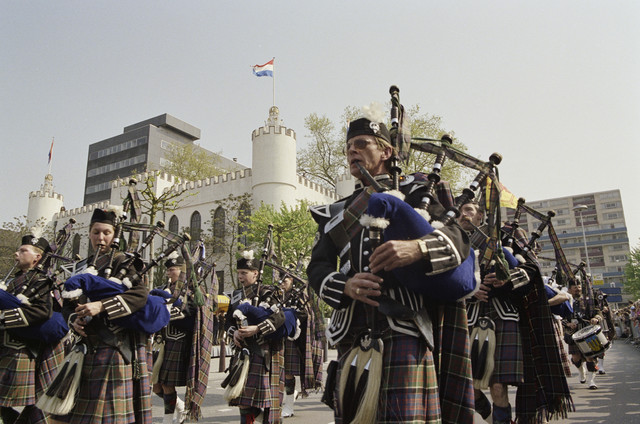 TLB023000349_001 - Het opleidingscentrum van de Aan- en Afvoertroepen in de Koning Willem II Kazerne wordt gesloten. Tilburg is vanaf dan geen garnizoensstad meer. Op Koninginnedag 30/04/1993 verlaten de laatste militairen Tilburg met een defile. De Tilburgse doedelzakband, geinspireerd op de doedelzakmuziek van de Schotse bevrijders van Tilburg in de 2e Wereldoorlog, The Dutch Pipes and Drums. Op de achtergrond Stadskantoor 2 (de zwarte doos) en het oude Paleis Raadhuis.