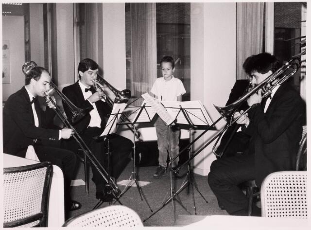 """036101 - Optreden van het """"Daniel Speer Trombone Consort"""" in de foyer van de Stadsschouwbrug. Daar had een ontvangst plaats na de onthulling van de vernieuwde gedenknaald Koning Willem II in 1987, op het Stadhuisplein, vlak bij de ingang van de Heikese kerk. Het nog prille klassieke ensemble bestond uit v.l.n.r. Gerard de Krom, leiding,  Gert-Jan Rongen, Joost Swinkels en Hans Mooren, studenten aan het Brabants conservatorium in Tilburg, destijds gevestigd in het Cenakel. Henri Aarts was de trombone-docent. Het ensemble was opgericht in 1985 en zou 18 jaar blijven bestaan, met succesvolle optredens in binnen- en buitenland, voor radio en TV enz."""