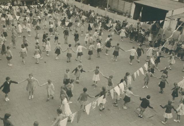 """651611 - Meisjesschool Vincentius. Tilburg. Op 1 mei 1961 werd het Gouden Jubileum van deze school gevierd. Tijdens het feest dansten de kleinste meisjes """"De Tovercirkel"""" , een ringelrei,  voor de genodigden.   Het bestuur van de parochie Hasselt - d.w.z. parochie van O.L. Vrouw van den Allerheiligste Rozenkrans - stichtte een nieuwe meisjesschool. In 1909 werd een bouwterrein aangekocht door pastoor Franciscus J.A. de Beer (voorzitter parochiebestuur).  Architect F.C. de Beer tekende het ontwerp. De bouwkosten bedroegen in 1910  fl.30.372,00 en de zusterschool werd opgeleverd in 1911. Tot 1911 volgden de meisjes uit de parochie Hasselt het lager onderwijs in de parchie Goirke. Pas in 1928 werd de nieuwe school aangesloten op het electriciteitsnet. Vanaf welke datum de school Vincentius werd genoemd, is onbekend."""
