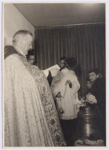 """044572 - De pastoor van het Heike wijdt op zondag 10 januar 1954 het Martinusklokje van de St. Maartenkapel aan de Oranjestraat. Het klokje weegt 75 kilo en draagt het opschrift: """"De Meester is daar en roept u"""""""