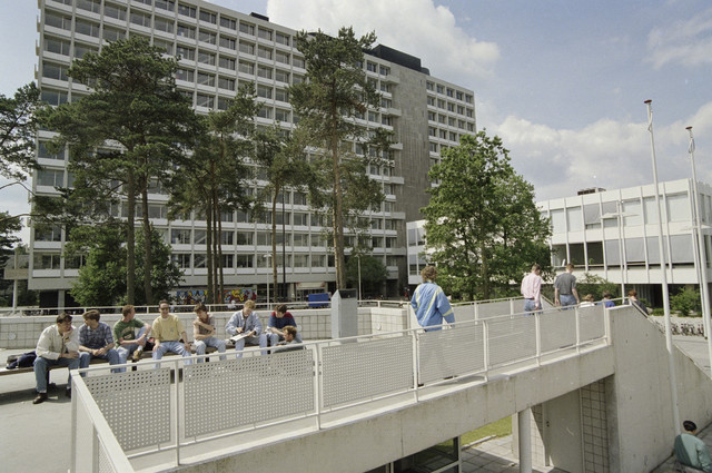 TLB023000334_003 - Vanuit de loopbrug naar de Universiteits Bibliotheek zicht op het Tjalling C. Koopmansgebouw met in de voorgevel de hoofdingang van de Universiteit.