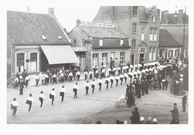 009023 - optocht H. Kindsheid parochie 't Goirke. Foto genomen aan het Wilhelminapark. op de achtergrond stalhouderij 'Wilhelmina' van J.J. Denissen, gevestigd Wilhelminapark nr. 127, die vroeger aan de Noordstraat heeft gezeten in het Noord-Brabants koffiehuis.