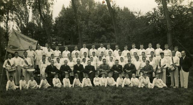 """093083 - Atletiek- en gymnastiekvereniging S.O.S. (Sport Ontwikkelt Spieren) werd opgericht vanuit het patronaat en `de Jonge Werkman` in 1931. De oprichtingsvergadering vond plaats in het Bondsgebouw aan het Oranjeplein op 25 maart 1932. Auteur H.W. Janson noemt in zijn 2Bijdrage tot de Geschiedenis van Goirle"""" als oprichters: Eduard Zebrechts, P. van den Berg, P. van Ostade en J. van Oirschot. In oktober 1933 is er sprake van een bloeiende vereniging. Vanaf juli 1934 werden ook niet-leden van het patronaat en """"de Jonge Werkman"""" toegelaten. Op de foto het bestuur, de leden en het nieuwe vaandel uit 1934. """"In burger"""" v.l.n.r. de bestuursleden Piet van Ostade, Pierre van den Berg, Willem Luijten, geestelijk adviseur kapelaan Briels, Frans Tra, Toon Weijters, Wim Snels en Theo Mallens. Geheel rechts trainer Pierre Sparidans. Geheel links tamboer Piet van den Hout en naast hem Kees Hendriks."""