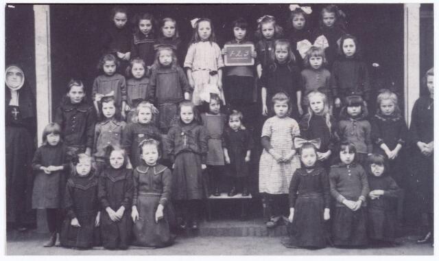 062052 - Basisonderwijs. Klassenfoto. Leerlingen van de eerste, tweede en derde klas van de R.K. lagere meisjesschool aan de St. Willibrordstraat omstreeks 1920. Het meisje met het bordje is Ria van Mensvoort. Links voor haar Rina van Mensvoort en recht voor haar Tilly van Mensvoort. Rechts achteraan, Jans Voermans-van Zon