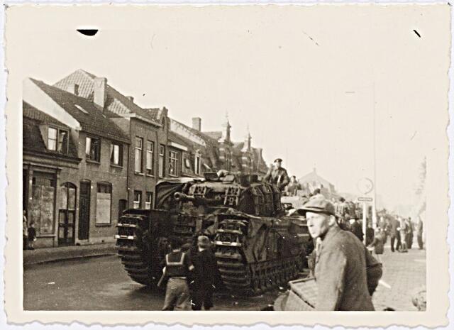 012243 - Tweede Wereldoorlog. Bevrijding. Britse tanks op de Bredaseweg. Diverse huizen zijn nog steeds dichtgetimmerd; de platen hadden de bewoners beschermd tijdens de felle strijd in het laatste oorlogsjaar