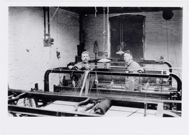 037833 - Textiel. Loonweverij van P. A. van Hest in de Zuid-Oosterdwarsstraat omstreeks 1920. De weverij, groot vijf bij tien vierkante meter, was gevestigd achter zijn woonhuis en bestond uit drie weefgetouwen, een ruwmolen en een scheerraam. Voordat Van Hest voor zichzelf begon, werkte hij als wever bij L. E. van den Bergh en bij André van Spaendonck. Op de foto links Petrus A. van Hest en rechts Bart Robben.