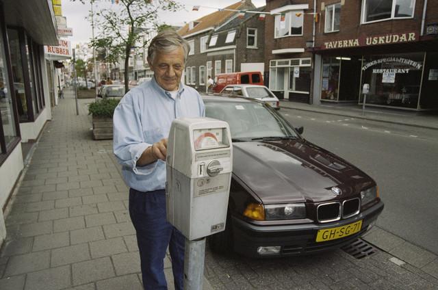 TLB023000936_003 - Automobilist Frans Smits stopt geld in een parkeermeter voor de deur van het gesloten Turks restaurant Taverna Üsküdar.