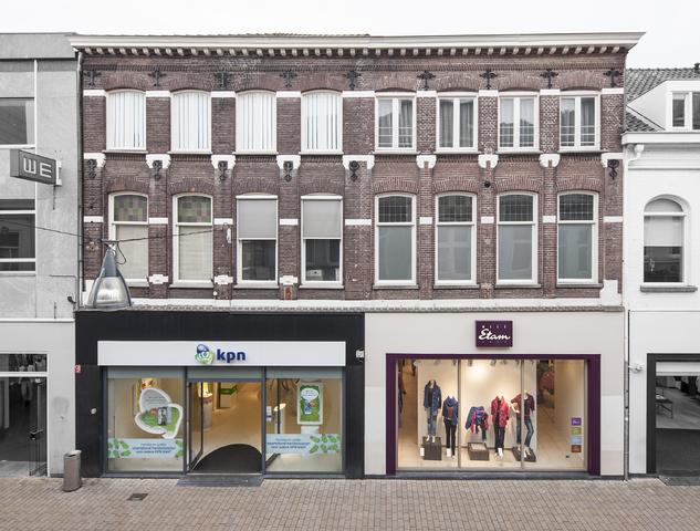 1611_044 - Heuvelstraat in Beeld. Dit MIP pand is ontworpen door architect C.F. van Hoof. Hier werd de eerste Tilburgse kassa in gebruik genomen, die tevens diende als prikklok voor het personeel. De fa. A.F. Uppenkamp opende op 20 september 1891, Heuvelstraat 46, een manufacturen zaak. In 1898 wordt het pand verbouwd en uitgebreid. Het art-nouveau-ontwerp is van de hand van architect Joling uit Amsterdam. In 1949 betrok Dora van de Ven de winkel op de begane grond; de familie Uppenkamp bleef op de bovenverdieping wonen en had daar een toonkamer tot 1969. Toen hield de zaak op te bestaan. In 1996 kwam de telefoonwinkel van KPN erin. Vanaf 1932 zat de fa. Van Haren, schoenen, hier tot 2004 toen zij plaats maakten voor Miss Etam.