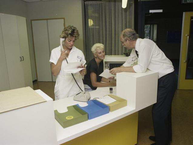 TLB023000091_003 - Ziekenhuismedewerkers achter balie van een secretariaat in het voormalige Maria Ziekenhuis Foto ter promotie van opleiding en Onderwijsexpositie
