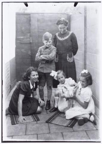 """049825 - Tilburgs gezin met geitje op binnenplaatsje. Foto van fotograaf frater Victorius van Gisbergen ( 1878-1944) uit:  """"je taalboek"""" van frater Victor van Nispen."""