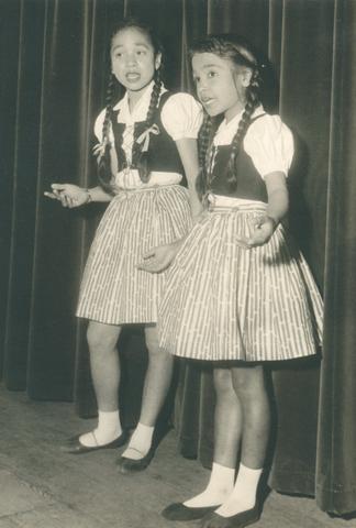 651620 - Meisjesschool Vincentius. Tilburg. De Indonesische klanken kwamen uit de gouden keeltjes van Inge Kraag (links) en Paula van Bavel. Het onderschrift bij deze foto is: Oto demmo roda tiga.