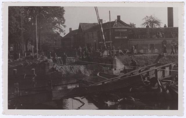 012339 - Tweede Wereldoorlog. Vernielingen. De restanten van de opgeblazen brug over het Wilhelminakanaal bij de Bosscheweg wordt opgeruimd om plaats te maken voor baileybrug. Foto genomen in de richting van 's-Hertogenbosch