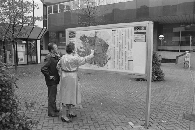 TLB023000017_001 - Bezoekers bekijken stadsplattegrond. Stadskantoor 1 op de achtergrond met links het toenmalige Gemeentelijk Informatiecentrum. Foto gemaakt ten behoeve van de Begrotingskrant van Tilburg, waarin wordt aangegeven dat de stad financieel gezond is als gevolg van het Tilburgs Model.