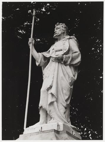 """067871 - De H. JOANNES de DOPER. Dit beeld werd geplaatst in 1892. Door wegverbreding in de jaren 30 en 70 stonden van de oorspronkelijke twintig beelden (allen langs de Bredaseweg) er nog veertien nog op hun oorspronkelijke plaats. En een nieuwe beeldenstorm dreigde. Door de aktie """"Heiligen gaan niet naar de hel"""" (prof. Van den Eerenbeemt) werden verdwenen beelden teruggehaald en gerestaureerd. Zij kwamen op nieuw gemetselde pijlers aan de zijde van de Noordhoekring te staan. Op 21 mei 1974 werd het herstelde beeld van Johannes de Doper plechtig onthuld door monseigneur Bluyssen. De beeldenstorm was ongedaan gemaakt. Een ingemetselde plaquette rechts van de ingang herinnert aan deze succesvolle redding. Zie ook fotonrs. 67854 en  67858.  Trefwoorden: Kunst, openbare ruimte."""