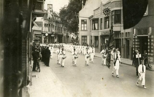 068654 - Drumband van leden van r.k. gymnastiekvereniging David marcheren door de Zomerstraat. Op de achtergrond de toren van de N.H. Pauluskerk.