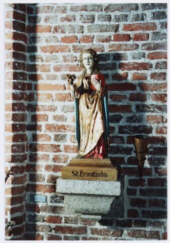 057053 - St. ERmelindis in de parochiekerk van Moergestel. De drie lelies in haar rechterhand symboliseren haar maagdelijkheid. In haar linkerhand draagt zij een gebedenboek. Het beeld werd vervaardigd in de 16e eeuw, maar kwam pas eeuwen later terecht in Moergestel.