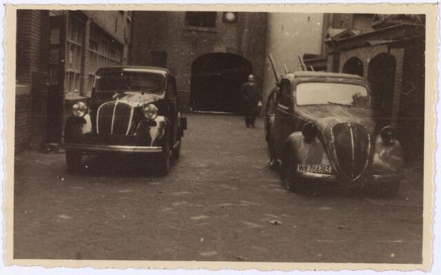 012454 - Tweede Wereldoorlog. Twee door de Duitsers achtergelaten personenauto's op de binnenplaats van textielfabriek Janssens - van Buren aan de Gasthuisstraat