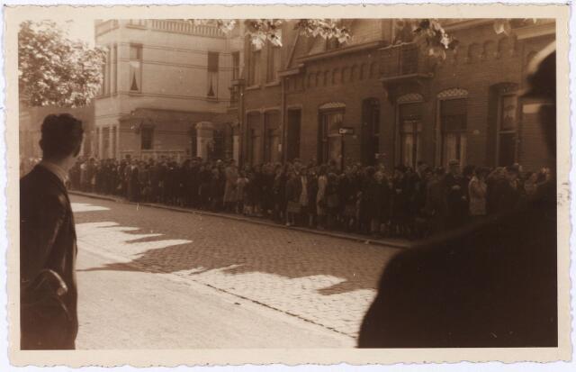 013955 - WO2 ; WOII ; Tweede Wereldoorlog. Distributie. Een lange rij wachtenden voor de Coöperatieve Tilburgse Melkinrichting (CTM) aan het Wilhelminapark eind 1944. De ingang lag echter om de hoek, in de Stedekestraat