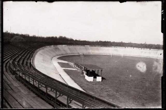 """047675 - De betonnen 400-meter baan van de """"Tilburgsche Wieler en Motorenclub"""" (TWEM) aan de Tilburgseweg. Voor de bouw werd op 31 maart 1921 door B. & W. een vergunning verstrekt. De baan werd ontworpen door de Duitse ingenieur Edmund Hellner uit Dresden, die ook wielerbanen ontwierp voor Dresden, New York, Antwerpen en Berlijn. De baan werd gebouwd door de firma Gebr. Schreinemacher. Nog in 1921 werd de baan opengesteld, maar spoedig bleken de mankementen: de baan was te steil en bovendien niet overdekt. Met vallen en opstaan wist men het bestaan te rekken tot begin jaren dertig. In september 1937 werd begonnen met de sloop. Het puin werd afgevoerd en gebruikt voor de Zuiderzeewerken."""