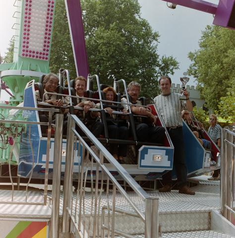 1237_001_010_005 - De Tilburgse kermis in juli 1995. De eigenaar van de ronddraaiende attractie Revolution heeft een prijs gewonnen in de categorie groot vermaak. Hij poseert met de trofee naast een karretje van zijn attractie, hierin zit waarschijnlijk de jury.