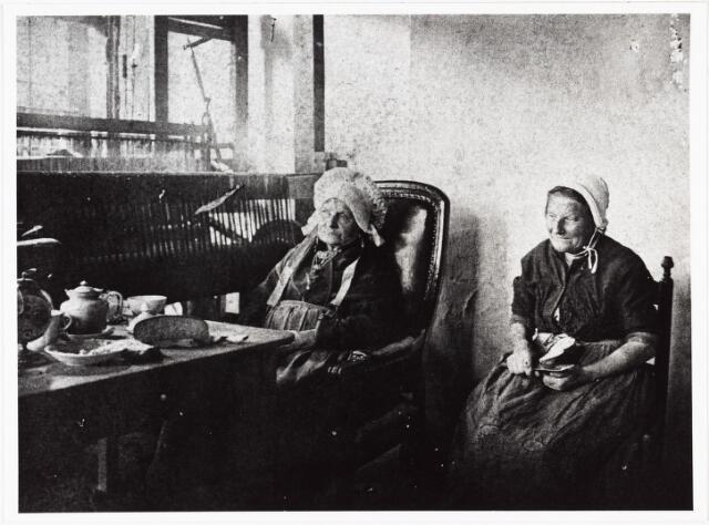 006963 - Annekee van Gorp poseert met haar dochter in de weefkamer van haar woning aan de Reitse Hoevenstraat t.g.v. haar honderste verjaardag op 14 juli 1905. Zij stamde uit en echte weversfamilie. anna van Pelt stapte op 22-jarige leeftijd in het huwelijk met arbeider-tuinman Bernardus van Gorp. Hij stierf al vroeg en Annekee kreeg de zorg over hun zeven kinderen, waarvan er twee op jonge leeftijd aan typhus overleden. In de jaren zeventig liet zij met haar twee weverszonen twee weverswoningen bouwen aan de Reitse Hoevenstraat (62 en 64). Deze woningen werden enige jaren geleden gerestaureerd.