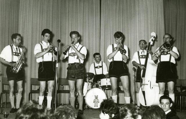 """200027 - De Tirolermuziekgroep """"de Alphenecho's"""", gefotografeerd tijdens een optreden in Goirle. De groep kwam uit Ooterhout en werd opgericht in 1959 door muzikanten van de Koninklijke Harmonie Oosterhout. Vanaf 1962 heette de muziekgroep, die bestaan heeft tot 1986, """"Die Alphenecho's"""". Van links naar rechts: Rinus Tielemans, Ad Roovers. Janus Schoormans (leider), Jack Weterings, Jan Kuppers, Jan Martens en Toon van Tilburg.  De groep was zeer bekend in Midden-Brabant en speelde o.a. als dansorkest in de Tilburgse schouwburg na een gala-optreden van Toon Hermans, tijdens de tentoonstelling Hart van Brabant, en bij de viering van het 750-jarig bestaan van de stad Oisterwijk."""