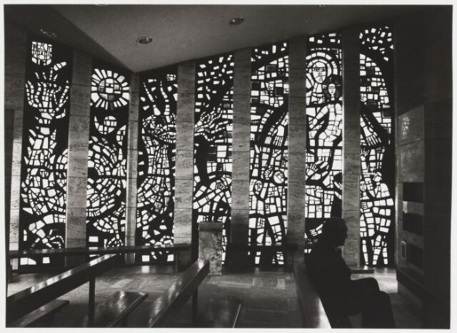 067935 - Glas-in-beton-raam van Daan WILDSCHUT (Grave 1913 - Bunde 1995) in de zuidwand van de gedachteniskapel O.L. VROUW TER NOOD (1964) aan de Kapelhof. Het is een symbolische uitbeelding van de Tilburgse bevolking, Maria's hulp afsmekend tegen de oorlog.    Trefwoorden: Kerkelijke kunst, openbare ruimte.