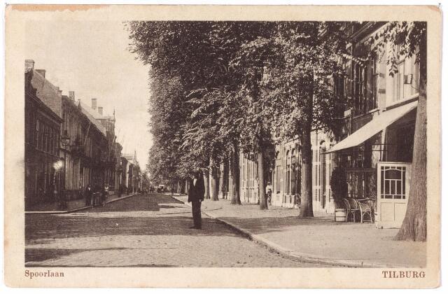 002130 - Spoorlaan vanaf de Heuvel. De Spoorlaan, aangelegd in 1867 en met keien over een breedte van vijf meter bestraat, heette aanvankelijk Zuider-Parallelweg. Bij raadsbesluit van 8.10.1881 werd de naam Spoorlaan vastgesteld, lopende 'van den overweg in den Noordhoek langs het spoor tot den Heuvel'.  Bij de aanleg van het hoogspoor werden de huizen aan de rechterzijde gesloopt. Bovendien kwam er een doorbraak op de Heuvel, waardoor de Spoorlaan verlengd werd tot aan de Ringbaan-Oost. Tot 1910 hoorde het gedeelte van de Spoorlaan op deze ansichtkaart, tot aan de Willem II-straat tot wijk N. De huizen hadden dan ook N-nummers. Van de Heuvel tot aan de Willem II-straat de huisnummers N. 245 t/m N 270. Vanaf de overkant van de straat richting Heuvel de nummers N. 271 t/m N 280. In 1910 werd een moderne nummering ingevoerd. De huizen tussen Heuvel en Willem II-straat kregen de nummers 2 t/m 62. Aan de overkant werden de nummers N 280 t/m N. 271 vervangen door de huisnummers 1 t/m 19. Het gedeelte van de Spoorlaan voorbij de Willem II-straat hoorde vóór 1910 tot de wijk M en had dus huisnummers die met een 'M' begonnen. Nadat de Spoorlaan was doorgetrokken tot aan de Ringbaan-Oost, waarbij de straatnaam Oude Bosscheweg verviel, werden de huizen opnieuw genummerd.
