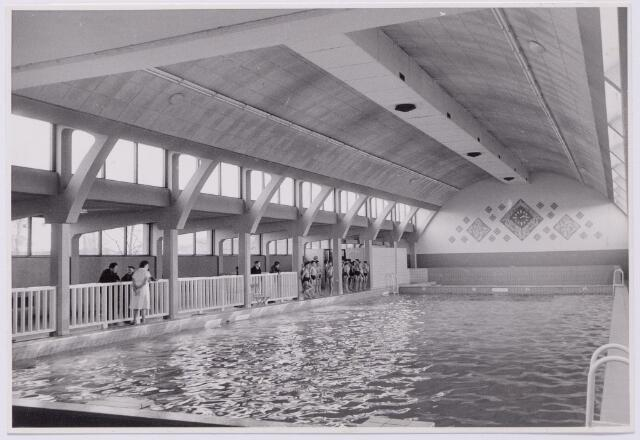 043563 - Interieur van het overdekte zwembad aan de Ringbaan-Oost. Reeds in 1938 bestonden er plannen voor de opening van een overdekt zwembad. Het ontwerp van architect Schijvens lag klaar. Toch duurde het tot 11 december 1954 voordat het eerste overdekte zwembad geopend werd. Architect van dit zwembad was het bureau Wesselo en Van Voort uit Bussum.Het bad bleek al spoedig een groot succes. 100 dagen na de openstelling was het zwembad al bezocht door 41.479 bezoekers.