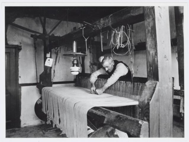 037459 - Textielnijverheid.  Thuiswever Frans van Geloven repareert een kettingdraad. Van Geloven, die woonde in de Tongerlose Hoefstraat, was de laatste praktiserende thuiswever in Tilburg, werkte voor de firma Enneking uit de Goirkestraat