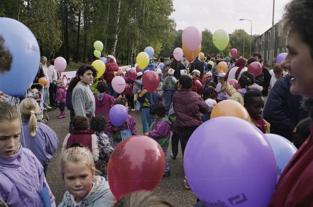 TLB023000382_004 - Kinderen met ballonnen tijdens de opening van de Karen Weening speeltuin. De Karen Weening speeltuin is een buitenspeeltuin in een bosgebied van 10.000 m², is prachtig aangelegd en wordt door een groep vrijwilligers uit de wijk i.s.m. Contour de Twern beheerd. De speeltuin is vernoemd naar de winnares van de ontwerpwedstrijd voor een speeltuin in Tilburg.