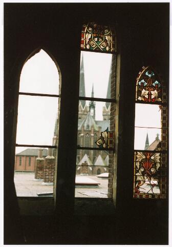 033353 - Detail van een raam van de kapel van het fratershuis aan de Bosscheweg, later Tivolistraat, met fragmenten van een glas in loodraam. De foto werd genomen tijdens de sloop in december 1987. Op de achtergrond de parochiekerk St. Joseph aan de Heuvel.