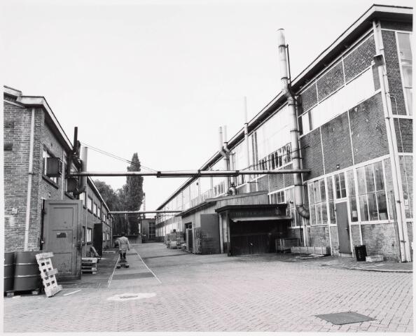 """034142 - Doorkijk Voltterrein in september 1978 gezien in de richting van de Voltstraat (westen). Links de oudste O hal gebouwd in 1947. Was vroeger algemeen- en ijzermagazijn. Rechts hal M (1929) waarin vroeger de afdlingen metaalwaren (vooraan) en de gereedschapmakerij (achteraan). De bomen staan in de tuin van het klooster van Avé Maria. Het gebouw achteraan, rechts van de boom, is het in 1961 gebouwde """"oliestook"""" ketelhuis."""