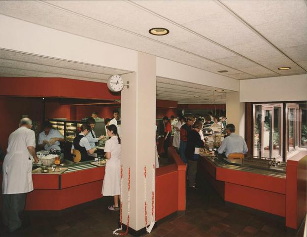 654144 - Elisabethziekenhuis. Gezondheidszorg. Aan de rechterkant in de hoofdgang ligt het personeelsrestaurant. Hier de uitgiftebalie. Bij de pilaar staat Nicole Huisman, ll verpleegkundige, die bij een verkeersongeluk op 19 maart 1993 om het leven kwam.