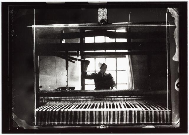 008487 - Thuiswevers. Vrouw aan weefgetouw, gefotografeerd door Henri Berssenbrugge (1873-1959). Op deze afdruk van een glasnegatief heeft B. een eigen afdruk van de foto nog een keer gereproduceerd en met strepen afgekaderd op de glasplaat.