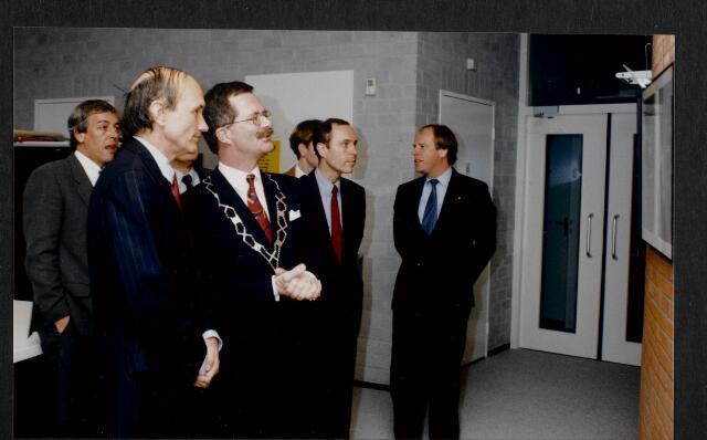 """91267 - Made en Drimmelen. De commissaris van de Koningin in Noord-Brabant (1987-2003) de heer Houben en de heer J. Elzinga, burgemeester van Made (1990-1997) kijken aandachtig naar het drieluik aan de muur van het zojuist officieel geopende Sociaal Cultureel Centrum """"De Mayboom"""" in Made."""