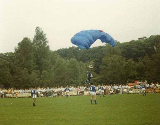 800087 - Voetbal. Openingswedstrijd van Taxandria tegen Willem II na de oplevering van de nieuwe tribune van voetbalvereniging Taxandria in Oisterwijk op 10 augustus 1988. Parachutisten brengen de wedstrijdbal.