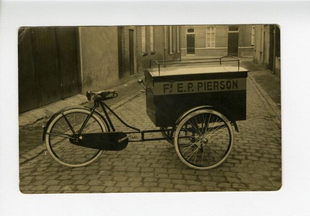 604201 - Bakfiets van de firma Pierson uit de Heuvelstraat te Tilburg. Pierson was een winkel in galanteriën en luxe artikelen, gevestigd aan de Heuvelstraat 99 en opgericht door Everardus Petrus Pierson (1853-1900). De oprichter overleed in 1900, hierna werd de zaak voortgezet door zijn weduwe Anna Pierson-van Laarhoven. De weduwe werd geassisteerd en vervolgens opgevolgd door haar zoon Cornelis Petrus Johannes Pierson (1883-1948). De winkel aan de Heuvelstraat handelde in verlichtingen, huishoudelijke artikelen, luxe artikelen, glas, kristal en porselein.  De afgebeelde bakfiets is van het merk Tilburgia.
